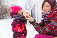 La mujer alimenta a bollo la pequeña muchacha Imágenes de archivo libres de regalías