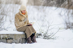 La mujer alista un libro en invierno Fotos de archivo libres de regalías
