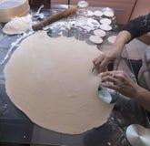 La mujer amasó la pasta e hizo los espacios en blanco Pasta, rodillo, tamiz, cuchara, vidrio en la tabla imagen de archivo