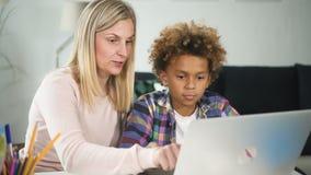 La mujer americana está mostrando a usar africano del muchacho del ordenador portátil, conexión a internet metrajes