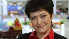 La mujer amistosa en rojo y negro sonríe en tienda metrajes