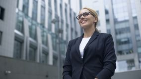 La mujer amistosa en traje encuentra socios comerciales, el intérprete o a la presentadora extranjero metrajes