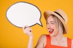 La mujer amistosa sonriente adorable en sombrero de paja y vestido de lujo rojo está sosteniendo banderas buble del discurso Fond Fotos de archivo
