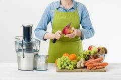 La mujer anónima que lleva un delantal, alista para comenzar a preparar el zumo de fruta sano usando el juicer eléctrico moderno foto de archivo