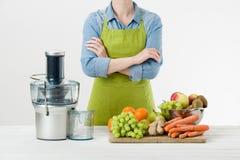 La mujer anónima que lleva un delantal, alista para comenzar a preparar el zumo de fruta sano usando el juicer eléctrico moderno fotografía de archivo libre de regalías