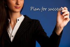 La mujer anima al equipo escribiendo un plan del éxito en la pantalla transparente Imágenes de archivo libres de regalías