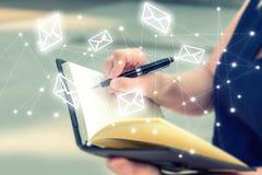 La mujer anota letras en el cuaderno para envía el mensaje sin el co imagen de archivo