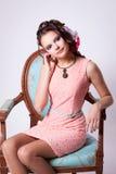 La mujer apacible en un vestido rosado y un pendiente verde del collar muestra Imagen de archivo libre de regalías