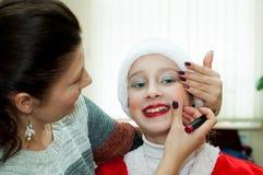La mujer aplica la cara del ` s de la muchacha de maquillaje Foto de archivo