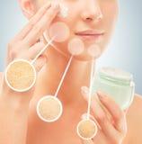 La mujer aplica la crema en cara Fotos de archivo libres de regalías