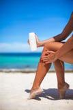 La mujer aplica la crema en sus piernas bronceadas lisas Imagenes de archivo