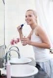La mujer aplica sus dientes con brocha Imagenes de archivo