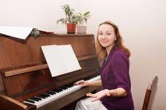 La mujer aprende jugar el piano Foto de archivo libre de regalías