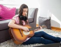 La mujer aprende tocar la guitarra clásica Imagen de archivo