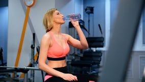 La mujer apta de los jóvenes con la toalla y la energía beben la relajación y la consumición en el gimnasio Concepto del deporte  metrajes