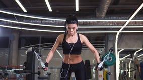 La mujer apta ejecuta ejercicio con la cruce del cable de la ejercicio-máquina en gimnasio metrajes
