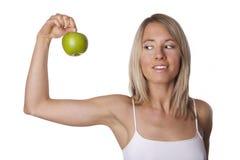 La mujer apta muestra la manzana Foto de archivo