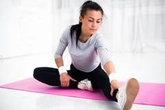 La mujer apta que hace estirar de la gimnasia de los aeróbicos ejercita su pierna y de nuevo a calentamiento en casa en la estera Fotografía de archivo