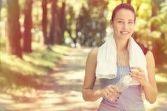 La mujer apta sonriente con la toalla blanca que descansa después de deporte ejercita Foto de archivo