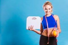 La mujer apta sostiene el pomelo de la escala del peso foto de archivo libre de regalías