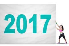 La mujer apta tira de la bandera con 2017 Imagen de archivo libre de regalías