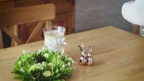 La mujer arregla las decoraciones hermosas de Pascua en la tabla