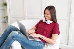 La mujer asiática con el auricular usando el ordenador portátil con relaja actitud imágenes de archivo libres de regalías