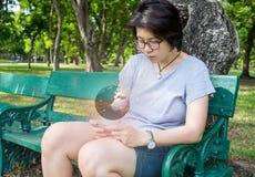 La mujer asiática conecta con el mundo entero usando su smartphone Foto de archivo libre de regalías