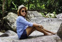 La mujer asiática de Tailandia se sienta en la roca Fotos de archivo libres de regalías
