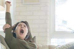 La mujer asiática del primer apenas despierta de una siesta en el sofá en fondo texturizado sala de estar Imagen de archivo libre de regalías