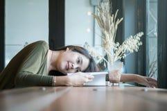La mujer asiática del primer mintió en el escritorio contrario de madera para leer un libro en cafetería con la cara feliz en la  Foto de archivo