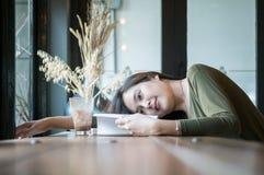 La mujer asiática del primer mintió en el escritorio contrario de madera para leer un libro en cafetería con la cara feliz en la  Fotografía de archivo