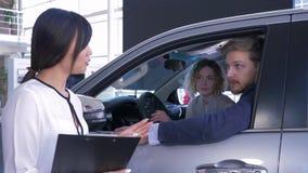 La mujer asiática del vendedor del coche consulta a la familia joven de los consumidores que se sienta en salón auto mientras que almacen de metraje de vídeo