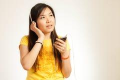 La mujer asiática disfruta de música Foto de archivo