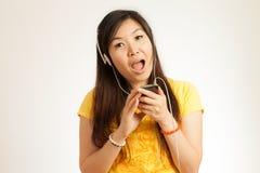 La mujer asiática disfruta de música Imagen de archivo libre de regalías