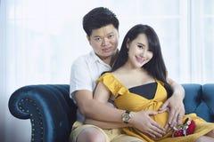 La mujer asiática embarazada de los jóvenes lleva a cabo sus manos en su vientre hinchado, Imagenes de archivo
