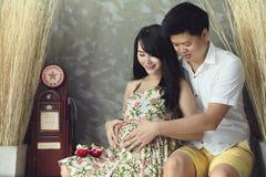 La mujer asiática embarazada de los jóvenes lleva a cabo sus manos en su vientre hinchado, Imágenes de archivo libres de regalías