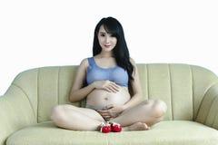 La mujer asiática embarazada de los jóvenes lleva a cabo sus manos en su vientre hinchado, Fotos de archivo
