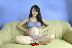 La mujer asiática embarazada de los jóvenes lleva a cabo sus manos en su vientre hinchado, Fotografía de archivo