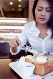 La mujer asiática está comiendo resma del hielo y el pan delicioso Foco encendido para Foto de archivo