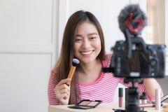 La mujer asiática está ofreciendo los cosméticos con las retransmisiones en directo, Blogg foto de archivo