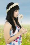 La mujer asiática está oliendo una flor fotos de archivo