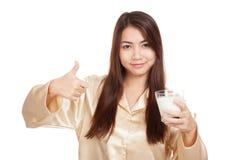 La mujer asiática feliz en pijamas muestra los pulgares para arriba con leche Foto de archivo