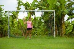 La mujer asiática feliz y emocionada joven en deporte viste jugar al fútbol que se divierte en el campo de fútbol de la selva con Fotografía de archivo libre de regalías