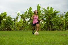 La mujer asiática feliz y emocionada joven en deporte viste jugar al fútbol que se divierte en el campo de fútbol de la selva con Imagen de archivo libre de regalías