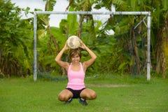 La mujer asiática feliz y emocionada joven en deporte viste jugar al fútbol que se divierte en el campo de fútbol de la selva con Foto de archivo libre de regalías