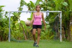 La mujer asiática feliz y emocionada joven en deporte viste jugar al fútbol que se divierte en el campo de fútbol de la selva con Imágenes de archivo libres de regalías