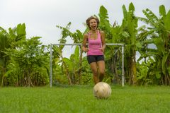 La mujer asiática feliz y emocionada joven en deporte viste jugar al fútbol que se divierte en el campo de fútbol de la selva con Imagenes de archivo