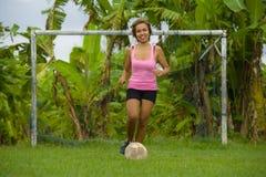La mujer asiática feliz y emocionada joven en deporte viste jugar al fútbol que se divierte en el campo de fútbol de la selva con Imagen de archivo