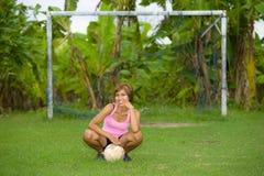 La mujer asiática feliz y emocionada joven en deporte viste jugar al fútbol que se divierte en el campo de fútbol de la selva con Fotos de archivo